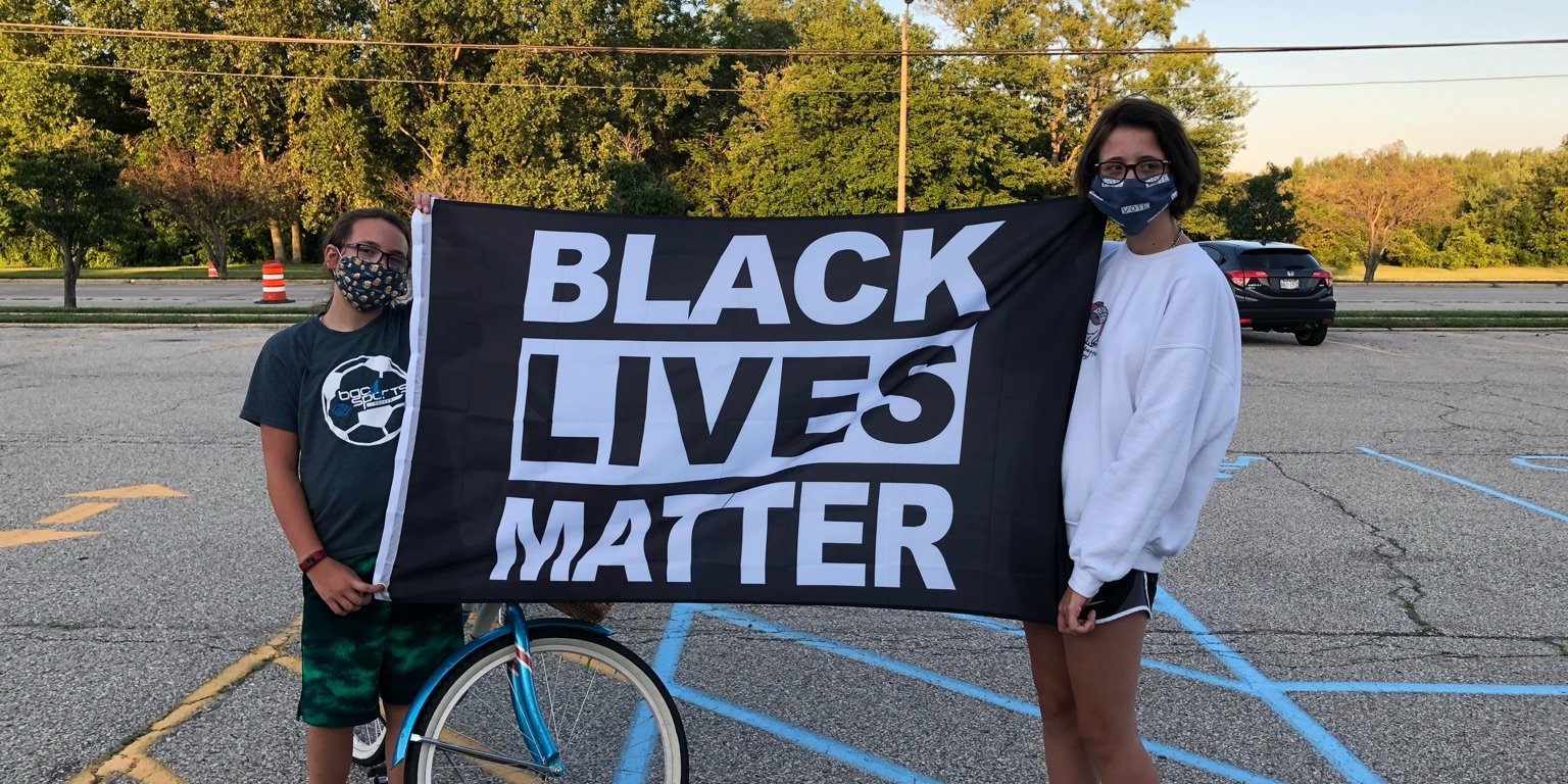 Zoe and Ruby hold BLM flag