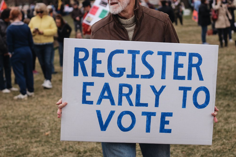 Man holding sign that says Register Early to Vote